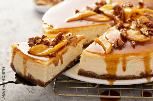 Obraz na plátně Apple caramel pecan cheesecake with dripping sauce with a slice cut out