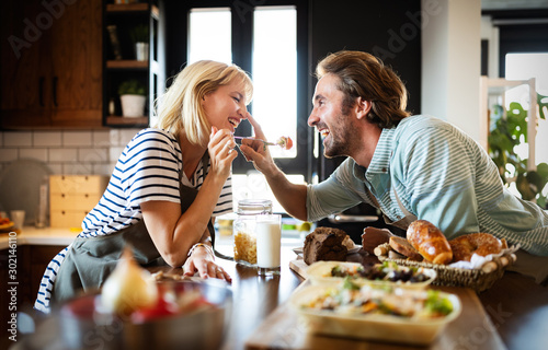 Fotografia Portrait of happy young couple cooking together in the kitchen at home