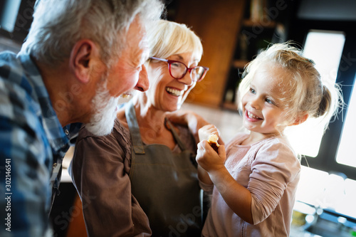Fototapeta Happy grandparents having fun times with children at home obraz