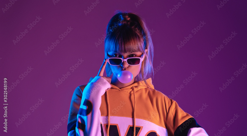 Fototapeta Pretty young 20s fashion teen girl model wear glasses blowing bubble gum looking at camera standing at purple studio background, igen teenager in trendy stylish night glow 80s 90s concept, portrait