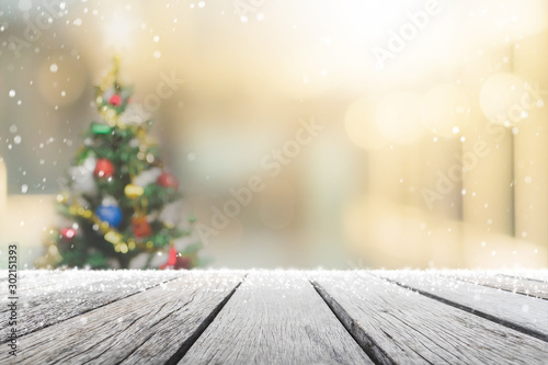 Obraz na plátně  Empty wood table top on blur with bokeh Christmas tree and new's year decoration on window banner background with snowfall - can be used for display or montage your products
