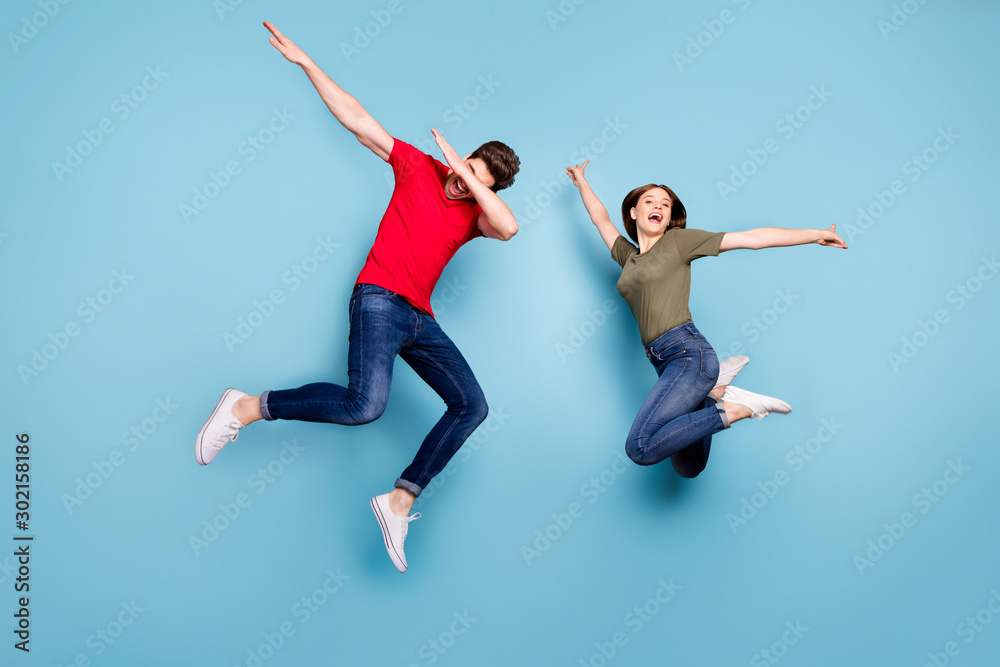 Fototapeta Full size photo of funky crazy two married people students fun jump man perform dab dancers woman raise hands wear green red t-shirt denim jeans sneakers isolated blue color background