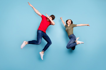 Fototapeta na wymiar Full size photo of funky crazy two married people students fun jump man perform dab dancers woman raise hands wear green red t-shirt denim jeans sneakers isolated blue color background