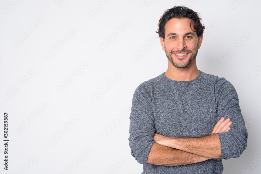Fototapeta Portrait of happy handsome Hispanic man smiling with arms crossed