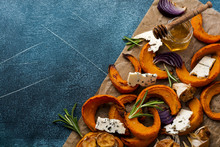 Slices Of Baked Pumpkin, Onions, Garlic, Spices And Slices Of Cheese Dorblu On Parchment Paper And Old Blue Stone Background. Top View.