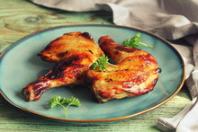 Grilled Chicken Leg Quarters With Crispy Golden Brown Skin, Parsley On White Plate On Dark Wooden Boards. Food Background. Top View