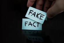 The Fact Is Replaced By A Fake. Substitution Of Concepts. A Man Changes The Signs With The Words Fact On Fake On A Black Background.