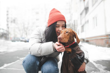 Happy Girl Hugs And Kisses A Beautiful Orange Dog On The Background Of A Winter Street And Buildings. Love To The Dog. Magyar Vizsla And Cute Girl Hug. Pets Concept