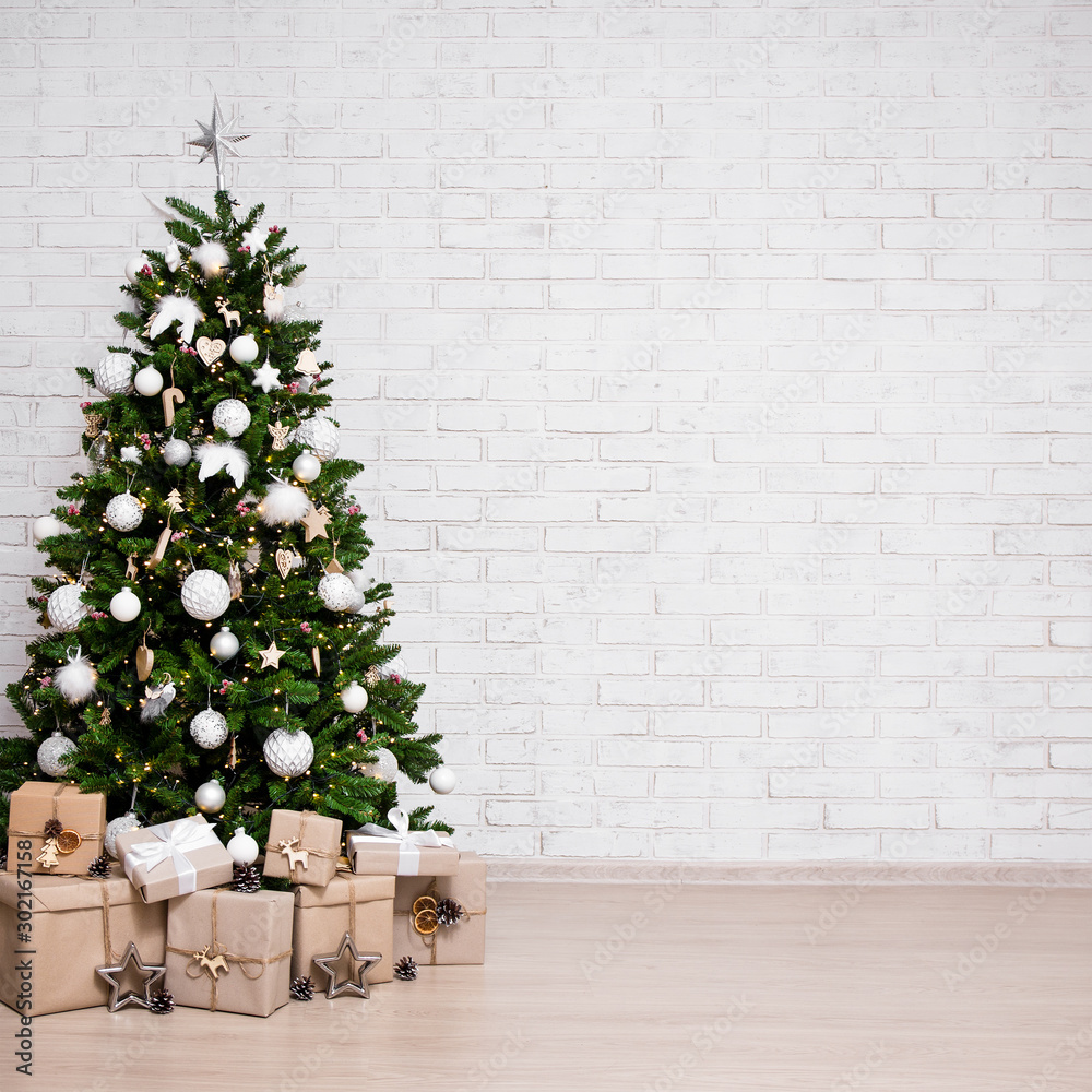 Fototapeta decorated christmas tree, heap of gift boxes over white brick wall with copy space