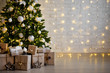 Leinwanddruck Bild christmas tree and heap of gift boxes - copy space over white brick wall with lights