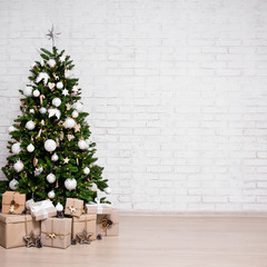 decorated christmas tree, heap of gift boxes over white brick wall with copy space