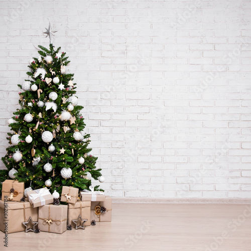 Fototapeta decorated christmas tree, heap of gift boxes over white brick wall with copy space obraz