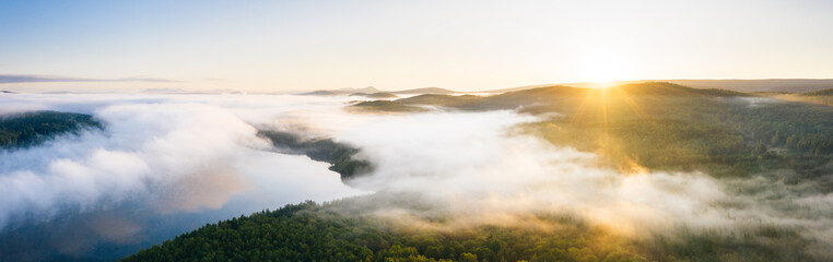 Fog over lake and taiga forest at sunrise, aerial view wide panorama. Nature landscape in Ural, Russia