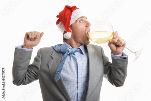Photo  Partying businessman in Santa hat taking a big gulp from a large wine glass at t