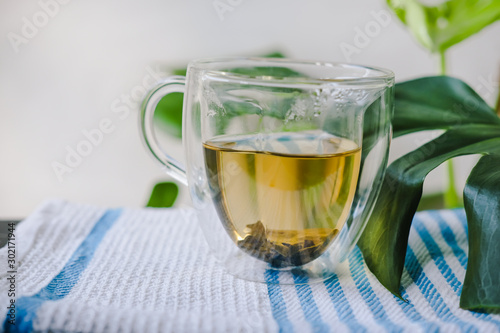 Garden Poster Tea glass cup of green tea on the waffle towel, glass cup of hot tea near part of the monstera leaf with blurred background, empty space at the left side, space for text