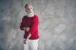 canvas print picture - Photo of attractive aged guy carefully fixing jumper sleeve looking empty space wear red pullover white trousers hipster santa clothes isolated grey color wall background