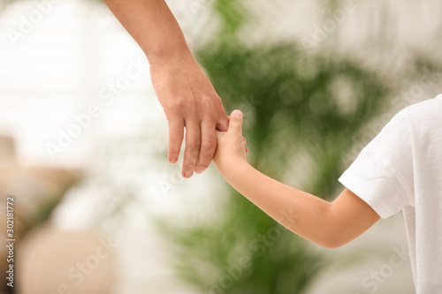 Fotografía Mother holding hands with her child indoors, closeup
