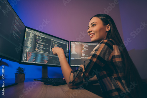 Fototapeta Profile side photo of cheerful positive nice pretty woman smiling toothily holding eye glasses sitting near screens looking through code written obraz