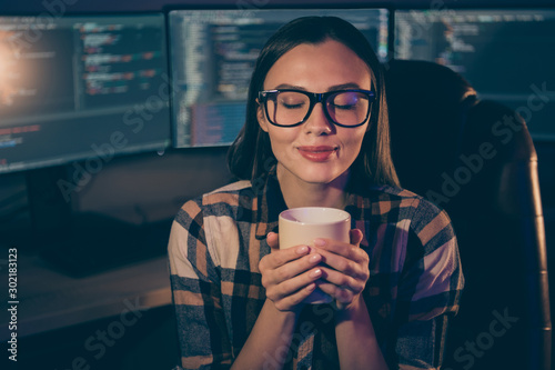 Obraz Photo of pleased satisfied cheerful joyful girl in spectacles enjoying aroma of freshly brewed coffee on the background of script java monitors - fototapety do salonu