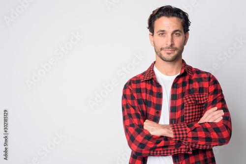 Fototapeta Portrait of handsome Hispanic hipster man with arms crossed obraz