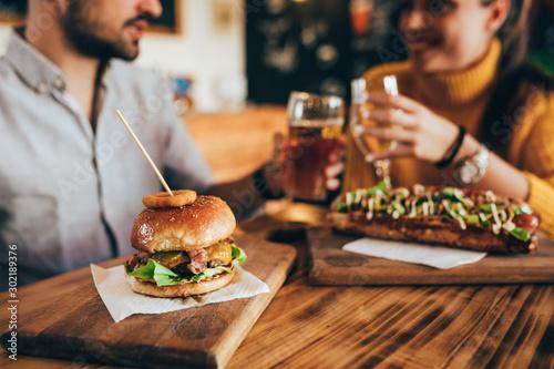 Fototapeta friends making a toast in bar, while eating fast food obraz