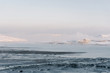 the snowy shore of the North Sea during low tide, the bottom becomes visible, and fog rises to the top on a frosty day in winter