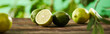 canvas print picture - panoramic shot of cut and whole limes on wooden surface