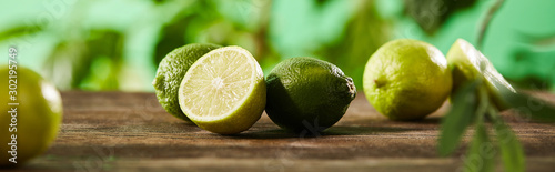 Obraz na plátne panoramic shot of cut and whole limes on wooden surface