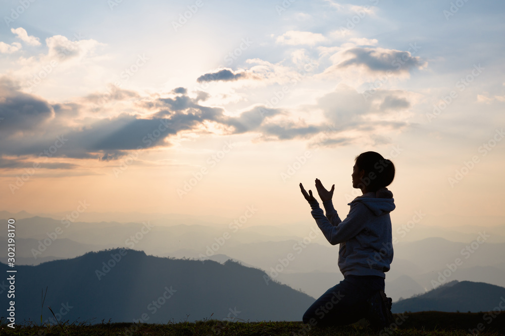 Fototapeta Silhouette of a woman with hands raised in the sunset concept for religion, worship, prayer and praise, Religious concepts
