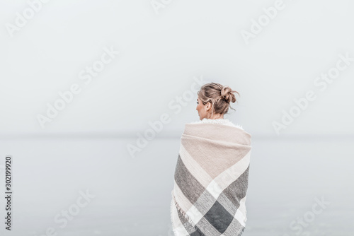 Obraz Pretty blonde woman wrapped in warm blanket standing on the cold autumn beach. - fototapety do salonu