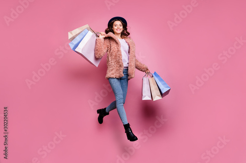 Full length photo of beautiful model millennial lady jumping high enjoy sales carry many packs store wear fluffy jacket retro blue hat jeans isolated pink background - 302204534