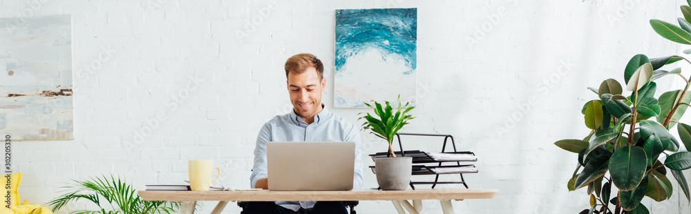 Fototapety, obrazy: Smiling freelancer using laptop at desk in living room, panoramic shot