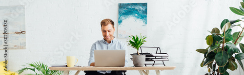 Stampa su Tela  Smiling freelancer using laptop at desk in living room, panoramic shot