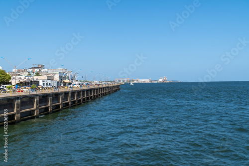 Fotografie, Obraz Sidewalk on the river bank of the city of Santarem, Para, Brazil and Rio Tapajos on sunny summer day in the amazon with blue sky