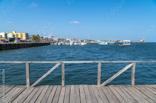 Fotografie, Tablou  Wooden pier bridge on Tapajos river on sunny summer day in amazon with colorful city of Santarem river bank in the background