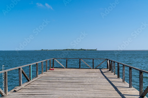 Fotografie, Tablou  Wooden pier bridge on sunny summer day in amazon with beautiful waters of Tapajos River in the city of Santarem, Para, Brazil