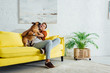 canvas print picture - Happy man playing with french bulldog on sofa in living room
