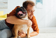 Smiling Man Hugging Funny French Bulldog On Floor In Living Room