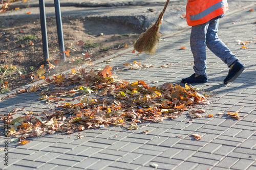 Pinturas sobre lienzo  A cleaning lady cleans the dead side of the maple leaves from the sidewalk