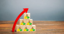 Wooden Blocks With The Image Of Money And Up Arrow. The Concept Of Profit Growth And Income. Profitability And Performance Business. Investments, Capital. Success