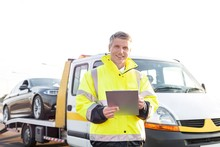 Tow Truck Driver Holding And Writing Report On Clipboard