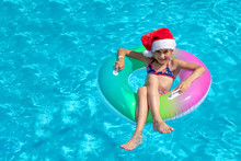 Kid Wearing Santa Claus Hat Are Swimming In A Blue Pool On A Bright Sunny Day And Smiling. Concept Of Happy New Year And Christmas. Space For Text,