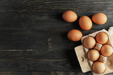 Chicken Eggs In Carton Box On Wooden Background, Space For Text