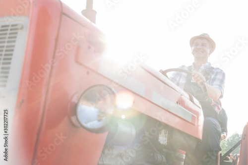 Obraz Mature farmer driving tractor in field - fototapety do salonu
