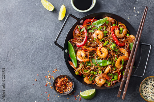 Valokuvatapetti Stir fry noodles with vegetables and shrimps in black iron pan