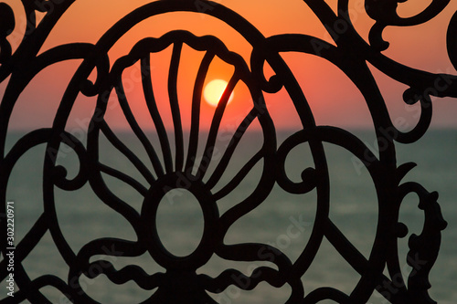 Photo  A beautiful Sunset is visible through a cast-iron openwork lattice