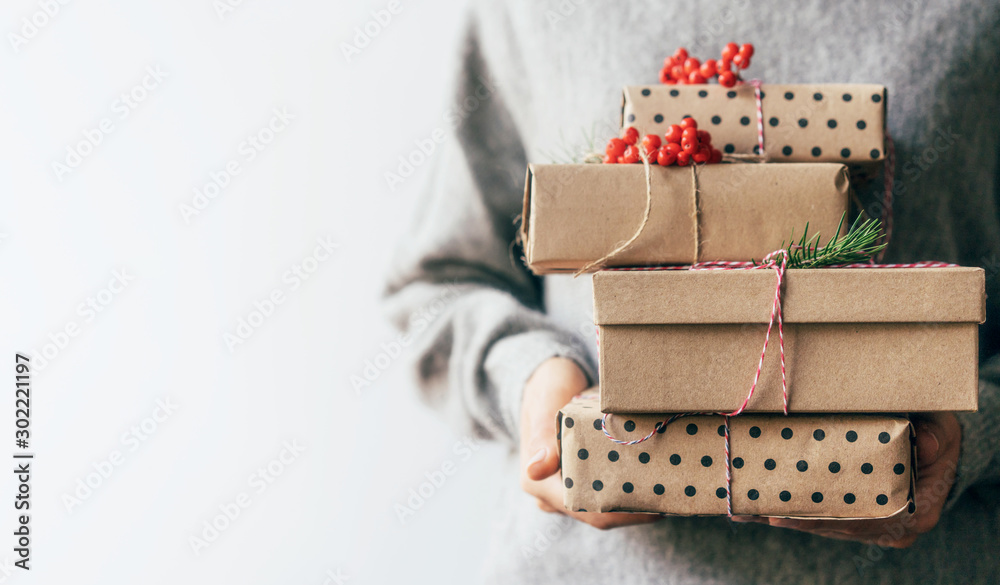 Fototapeta Elegant female hands holding gift boxes in plain brown paper decorated with red berries. Christmas concept. Copy space for text on a white background.