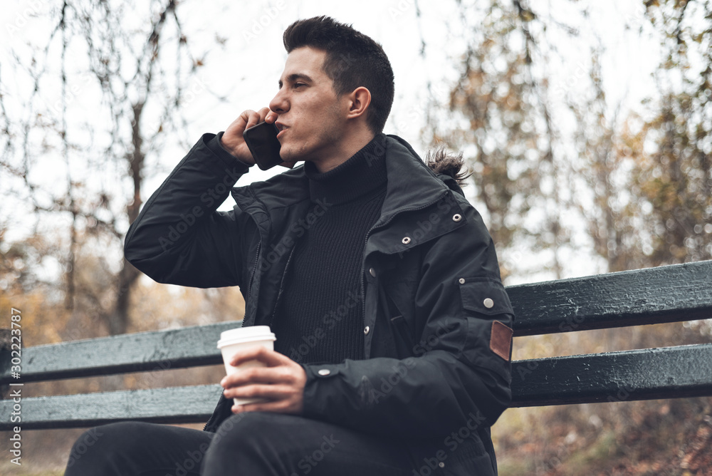 Fototapeta Young Smiling Man Wearing Coat Talking On Cellphone And Drinking Takeaway Coffee In Autumn park .