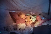 Little Girl Lying In A Teepee, Sleeping With The Flashlight In Dark Room With Toys And Pillows. Look Cute, Holding Teddy Bear. Home Comfort, Childhood, Christmas Holidays, Sweet Dreams Time.