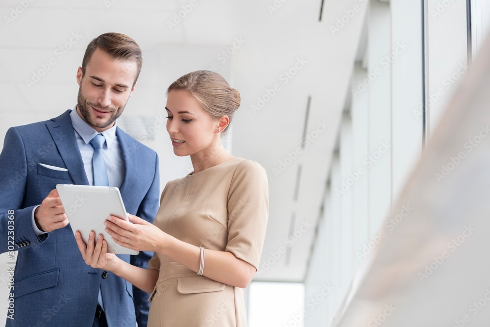 Fototapeta Bsinesswoman showing digital tablet to colleague in office